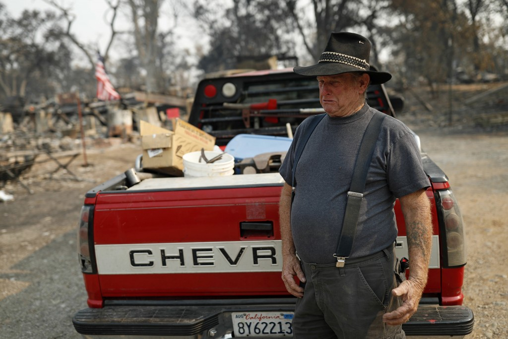 Ed Bledsoe cries after searching through what remains of his home, Monday, Aug. 13, 2018, in Redding, Calif. Bledsoe's wife, Melody, great-grandson Ja...