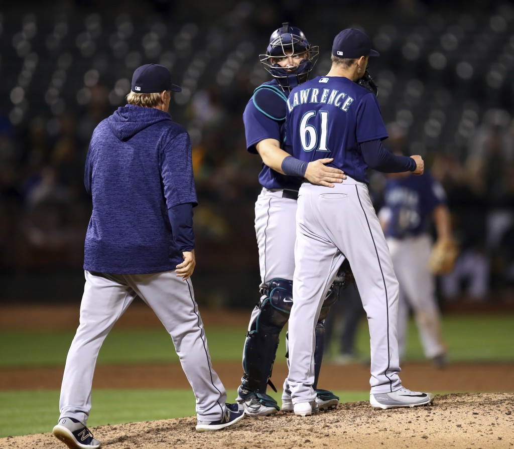 Seattle Mariners pitching coach Mel Stottlemyre, left, and catcher Mike Zunino, center, meet Casey Lawrence (61) in the sixth inning of a baseball gam...