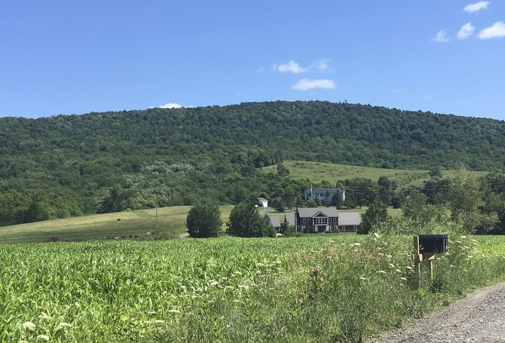 This July 18, 2018 photo shows a country road with views of rolling hills and forests of green trees behind the spacious home, in the far background, ...