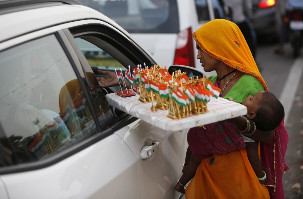 A woman sells Indian national flag memorabilia on the eve of Independence Day in Lucknow, India, Tuesday, Aug. 14, 2018. (AP Photo/Rajesh Kumar Singh)