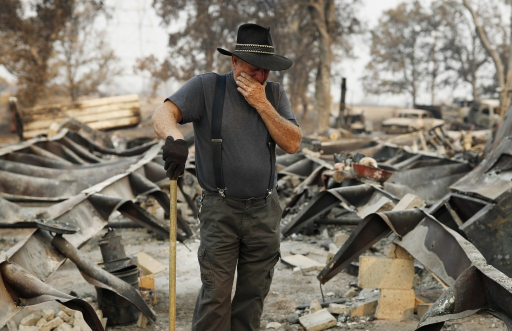 Ed Bledsoe tries to hold back tears as he searches through what remains of his home, Monday, Aug. 13, 2018, in Redding, Calif. Bledsoe's wife, Melody,...
