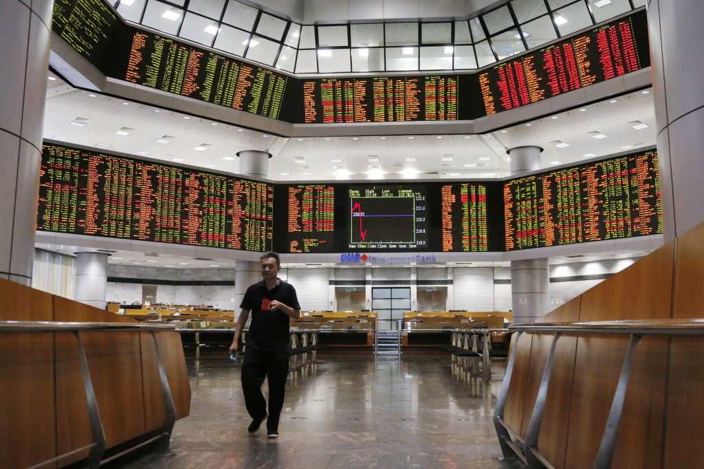 An investor walks in front of trading boards at a private stock market gallery in Kuala Lumpur, Malaysia, Tuesday, Aug. 14, 2018. Most Asian stock mar...