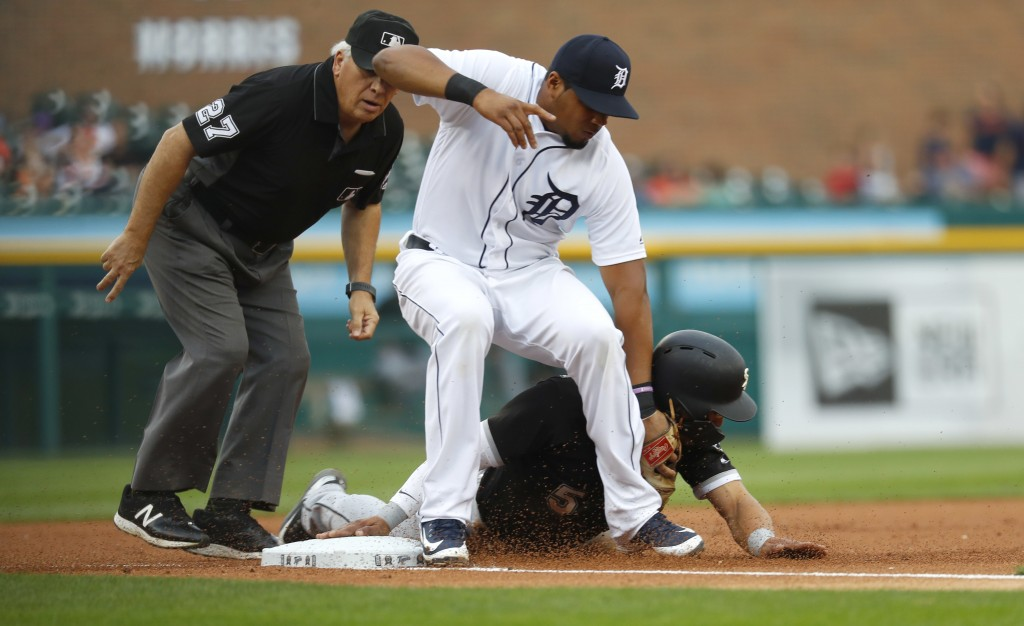 Chicago White Sox's Yolmer Sanchez steals third base as Detroit Tigers third baseman Jeimer Candelario applies a late tag while umpire Larry Vanover l...