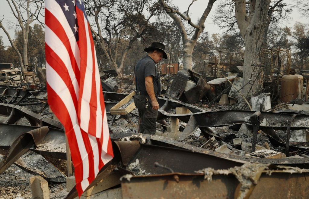 Ed Bledsoe searches through what remains of his home, Monday, Aug. 13, 2018, in Redding, Calif. Bledsoe's wife, Melody, great-grandson James Roberts a...