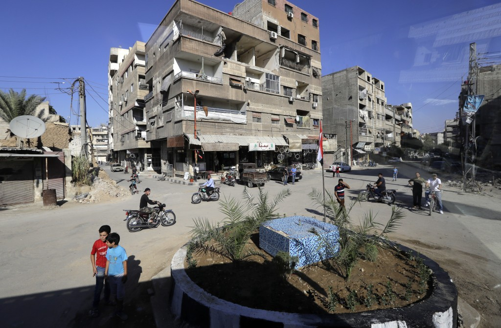 In a picture taken through a bus window, people drive their motorcycles in Damascus, Syria, Monday, Aug. 13, 2018. Syrian government officials vowed M...