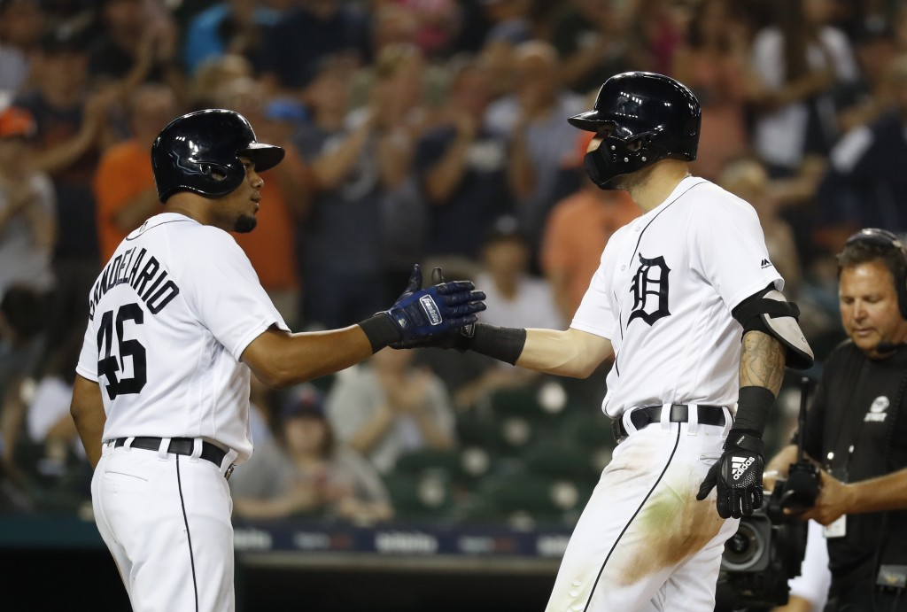 Detroit Tigers' Nicholas Castellanos, right, celebrates his two-run home run with Jeimer Candelario (46) in the seventh inning of a baseball game agai...
