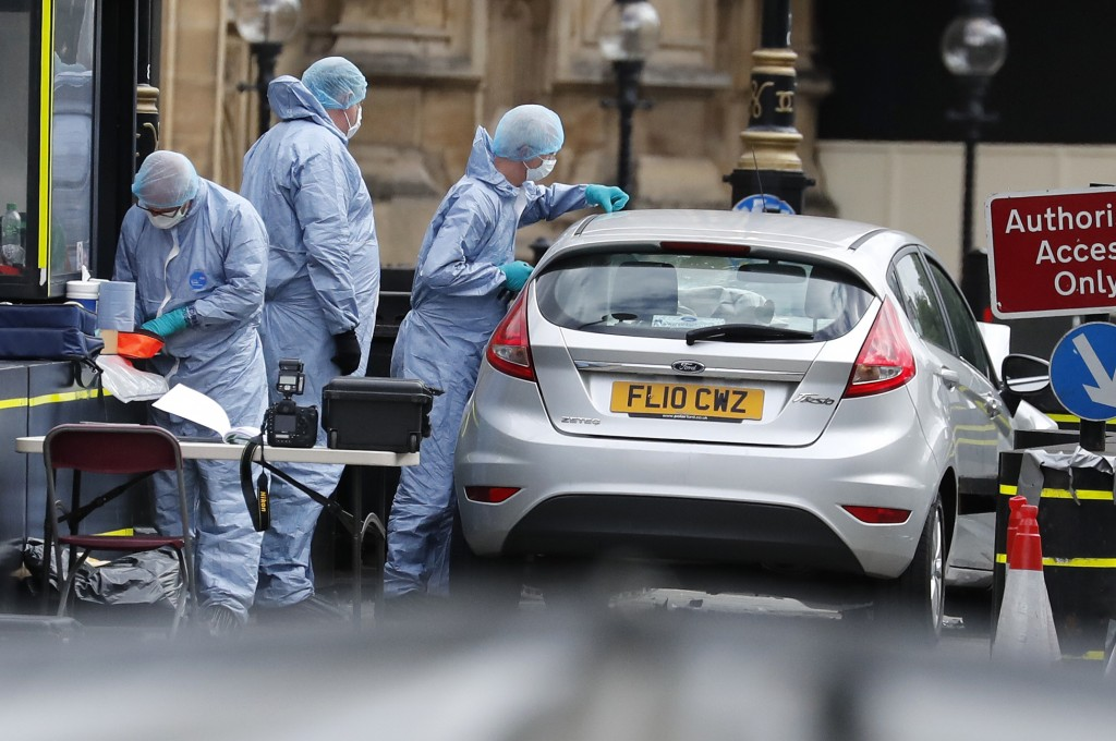 Forensics officers work near the car that crashed into security barriers outside the Houses of Parliament in London, Tuesday, Aug. 14, 2018. Authoriti...