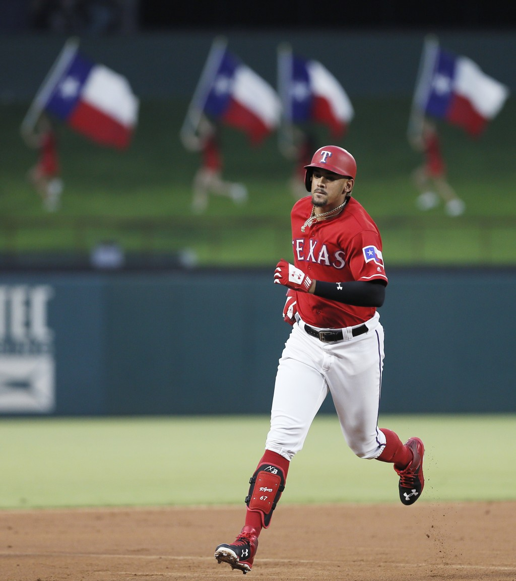 Texas Rangers' Ronald Guzman rounds the bases after hitting a solo home run during the third inning of a baseball game against the Arizona Diamondback...
