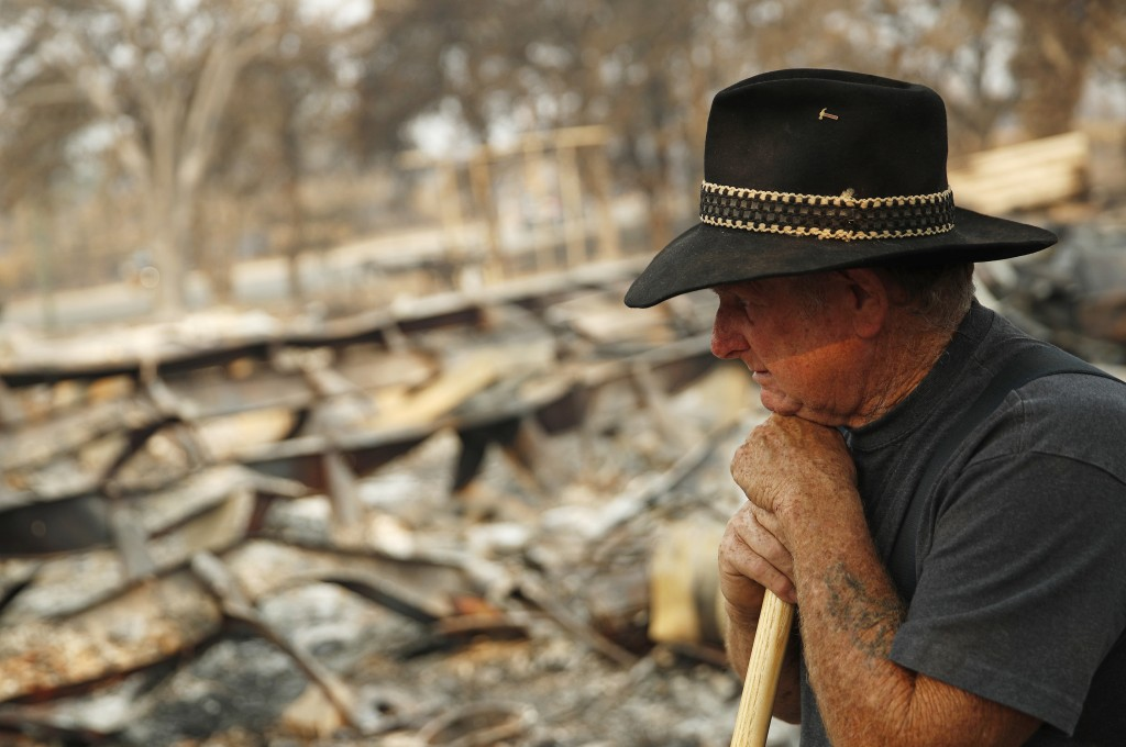 Ed Bledsoe rests as he searches through what remains of his home, Monday, Aug. 13, 2018, in Redding, Calif. Bledsoe's wife, Melody, great-grandson Jam...