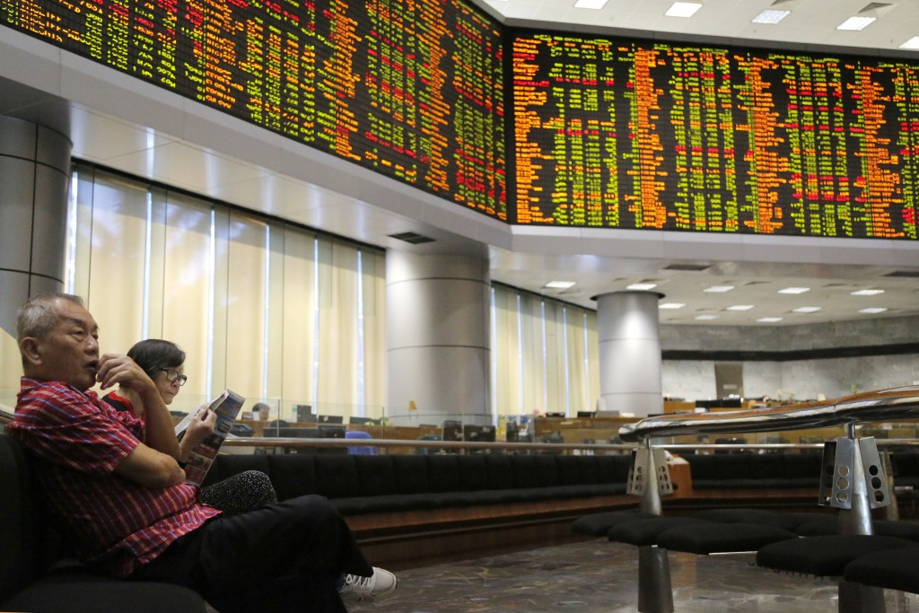 Investors sit in front of trading boards at a private stock market gallery in Kuala Lumpur, Malaysia, Tuesday, Aug. 14, 2018. Most Asian stock markets...