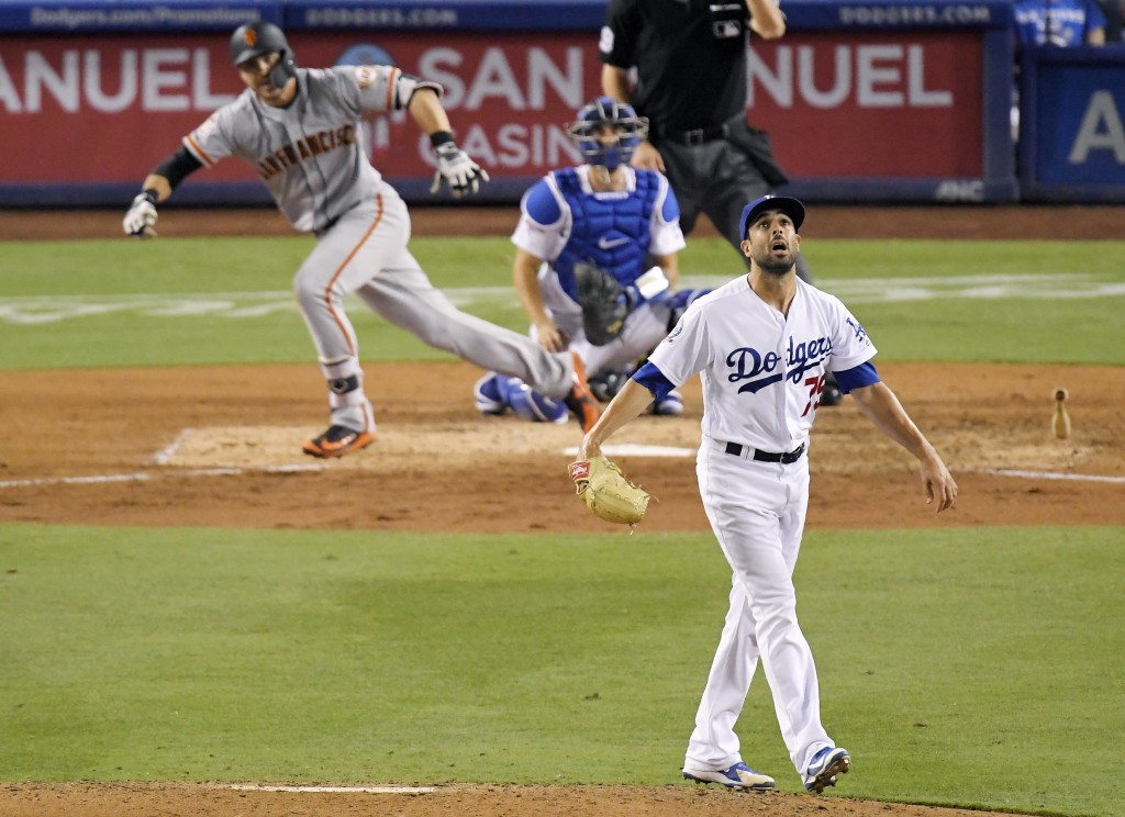San Francisco Giants' Chase d'Arnaud, left, hits a single as Los Angeles Dodgers relief pitcher Scott Alexander, right, watches along with catcher Aus...