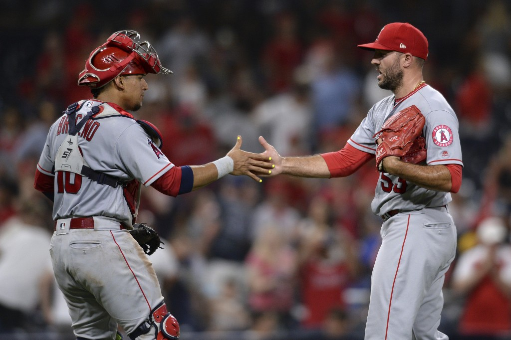 Los Angeles Angels' Jose Briceno and Blake Parker celebrate after recording the last out of the 10th inning and defeating the San Diego Padres in a ba...