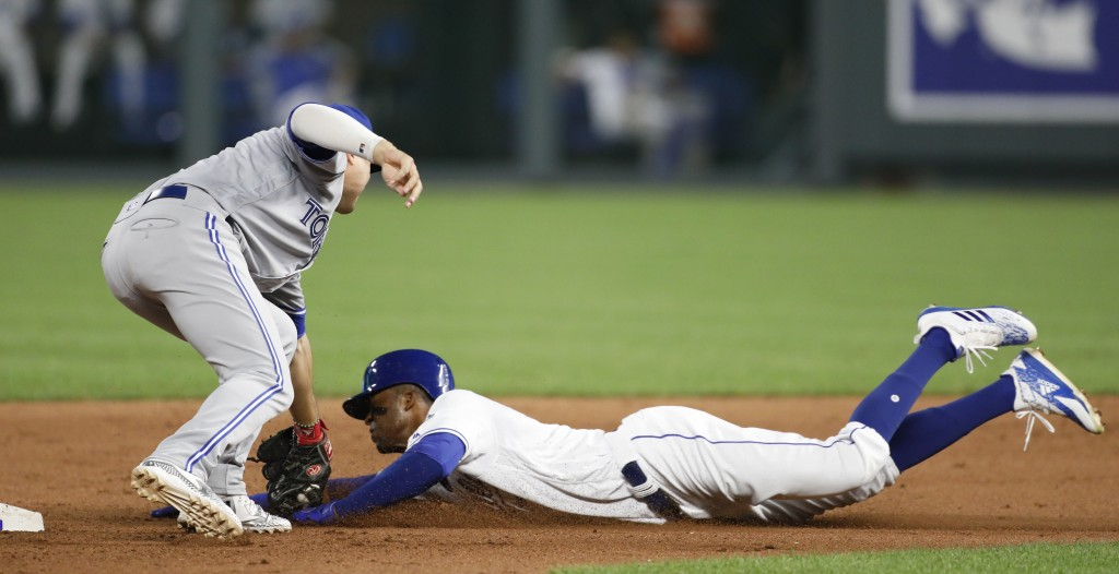 Toronto Blue Jays shortstop Aledmys Diaz, left, tags out Kansas City Royals' Rosell Herrera, right, as he attempts to steal second base in the sixth i...