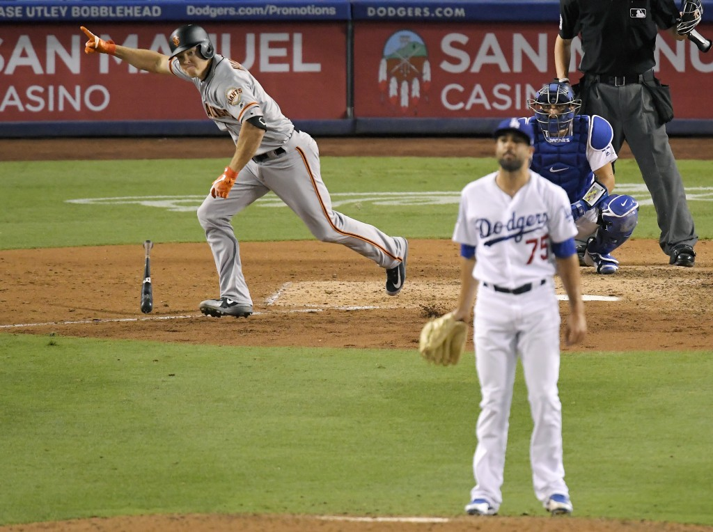 San Francisco Giants' Nick Hundley, left, celebrates as he hits a two-RBI single as Los Angeles Dodgers relief pitcher Scott Alexander, center, watche...
