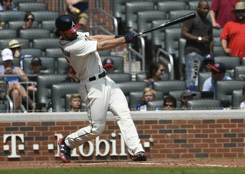 Atlanta Braves shortstop Charlie Culberson hits a fly ball to center field for a double during the sixth inning of the first baseball game in a double...