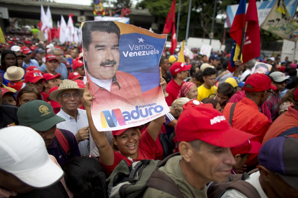 A supporter of Venezuela's President Nicolas Maduro holds up his picture during a rally in Caracas, Venezuela, Monday, Aug. 13, 2018. The United Socia...