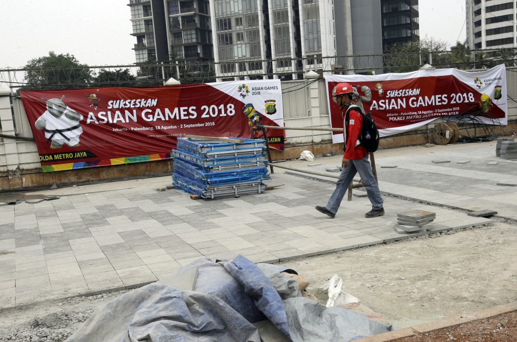 In this July 26, 2018 photo, a worker walks on the sidewalk which is being renovated ahead of the 2018 Asian Games at the main business district in Ja...