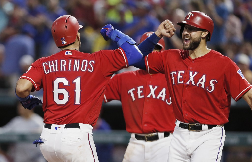 Texas Rangers' Robinson Chirinos (61) is congratulated by Joey Gallo, right, after hitting a three-run home run during the fourth inning of a baseball...