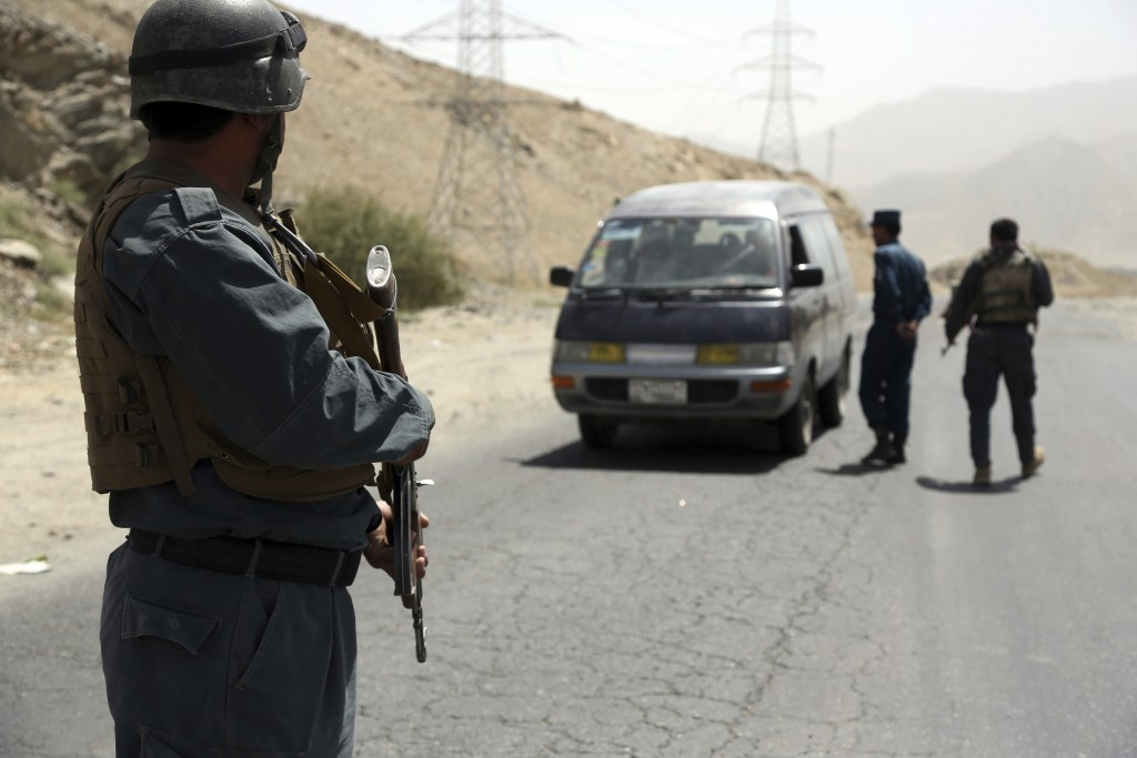 Afghan police officers search a vehicle at a checkpoint on the Ghazni highway, in Maidan Shar, west of Kabul, Afghanistan, Monday, Aug. 13, 2018. A Ta...