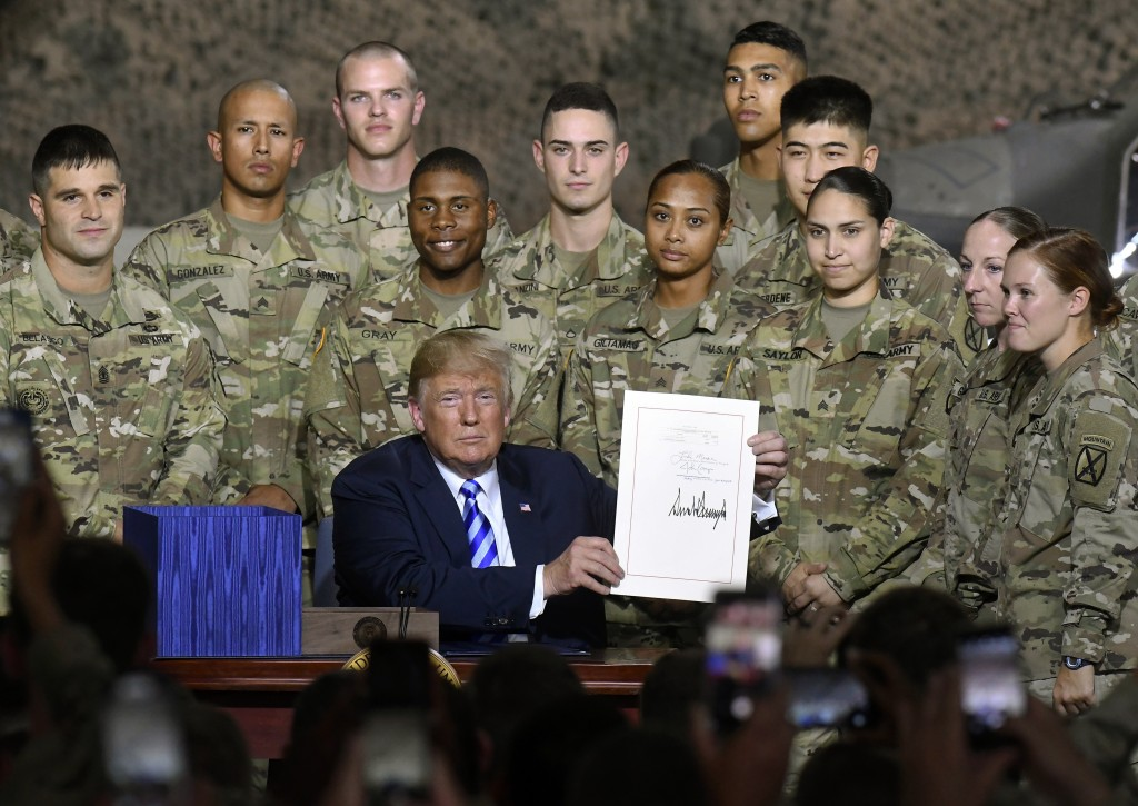President Donald Trump signs the John McCain National Defense Authorization Act for the Fiscal Year 2019, during a signing ceremony Monday, Aug. 13, 2...
