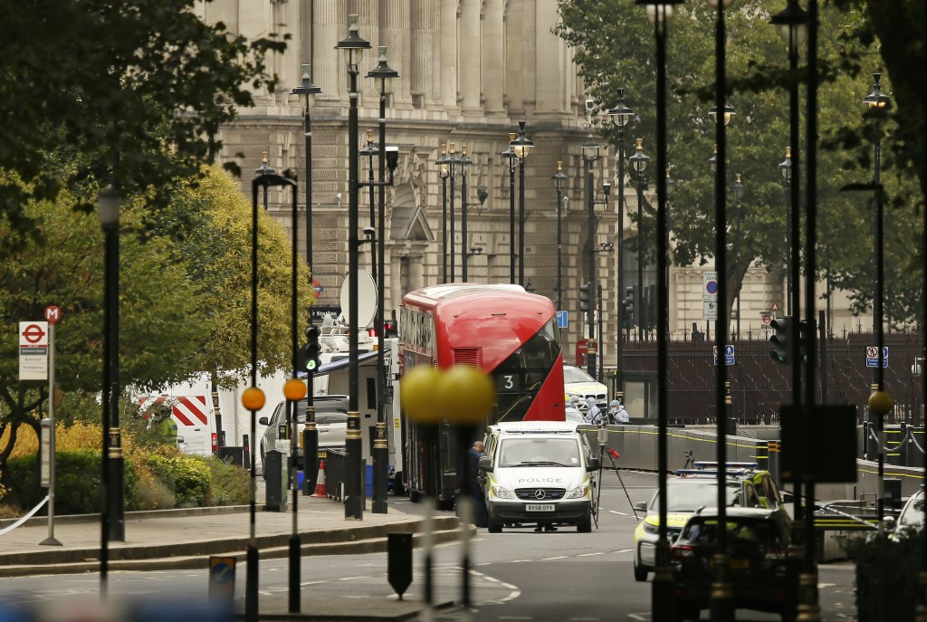 A forensics officer works near the scene near of a car that crashed into security barriers outside the Houses of Parliament to the right of a bus in L...