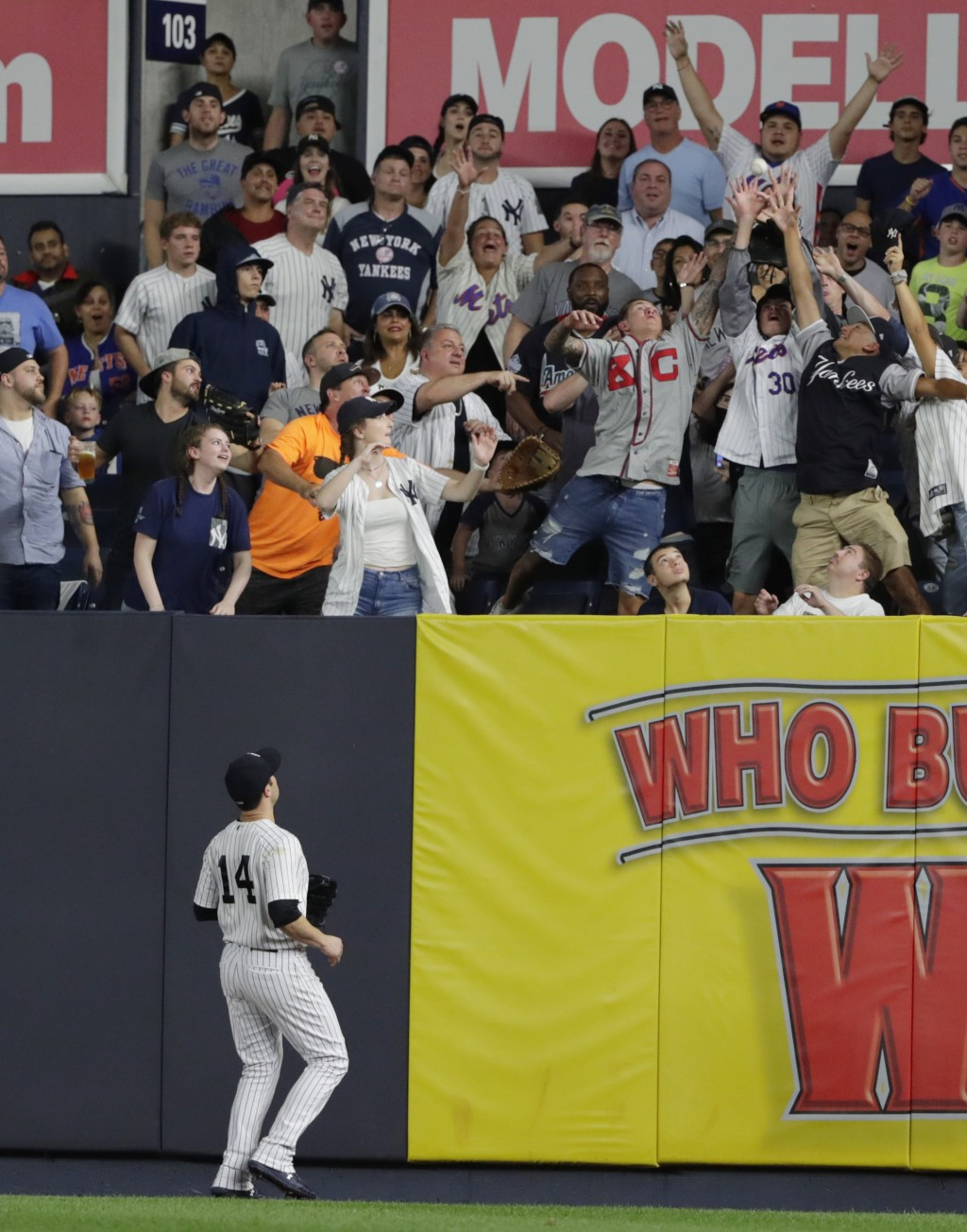 New York Yankees Neil Walker (14) watches as fans attempt to catch a ball hit by New York Mets' Brandon Nimmo for during the seventh inning of a baseb...