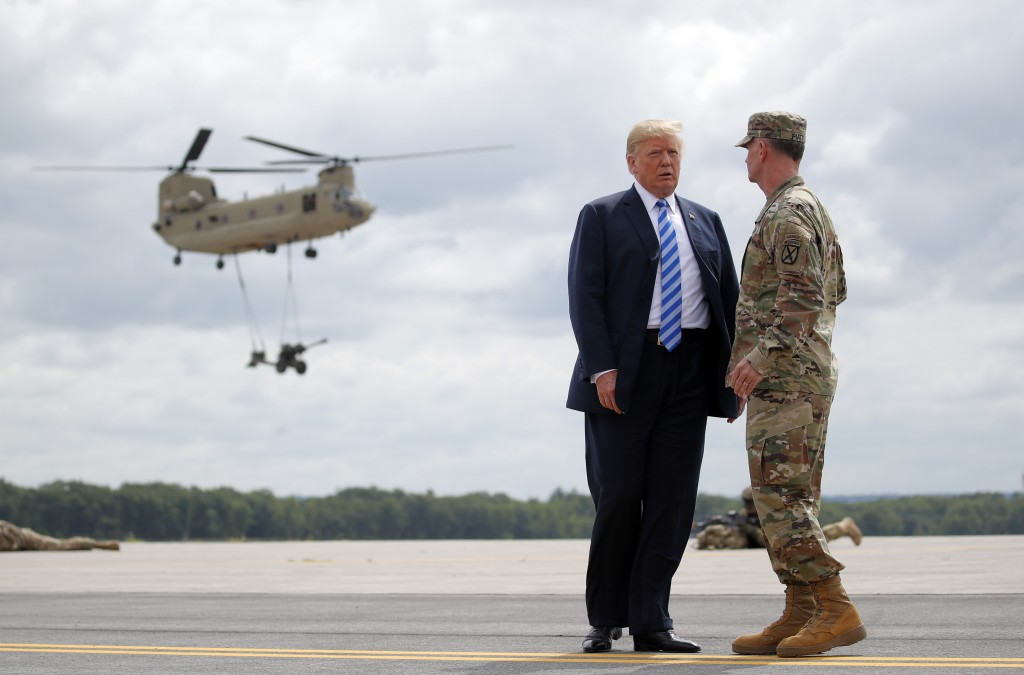 President Donald Trump talks with Maj. Gen. Walter Piatt as they watch an air assault exercise at Wheeler-Sack Army Air Field in Fort Drum, N.Y., Mond...