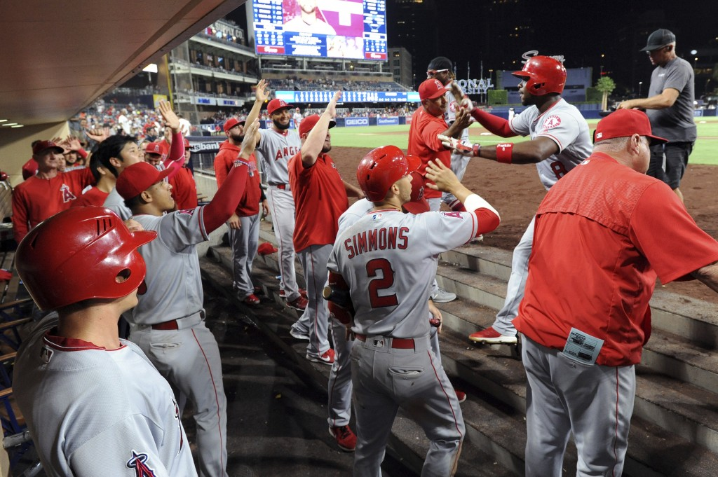 Los Angeles Angels' Justin Upton (8) is greeted at the dugout after hitting a two-run home run during the 10th inning of a baseball game against the S...