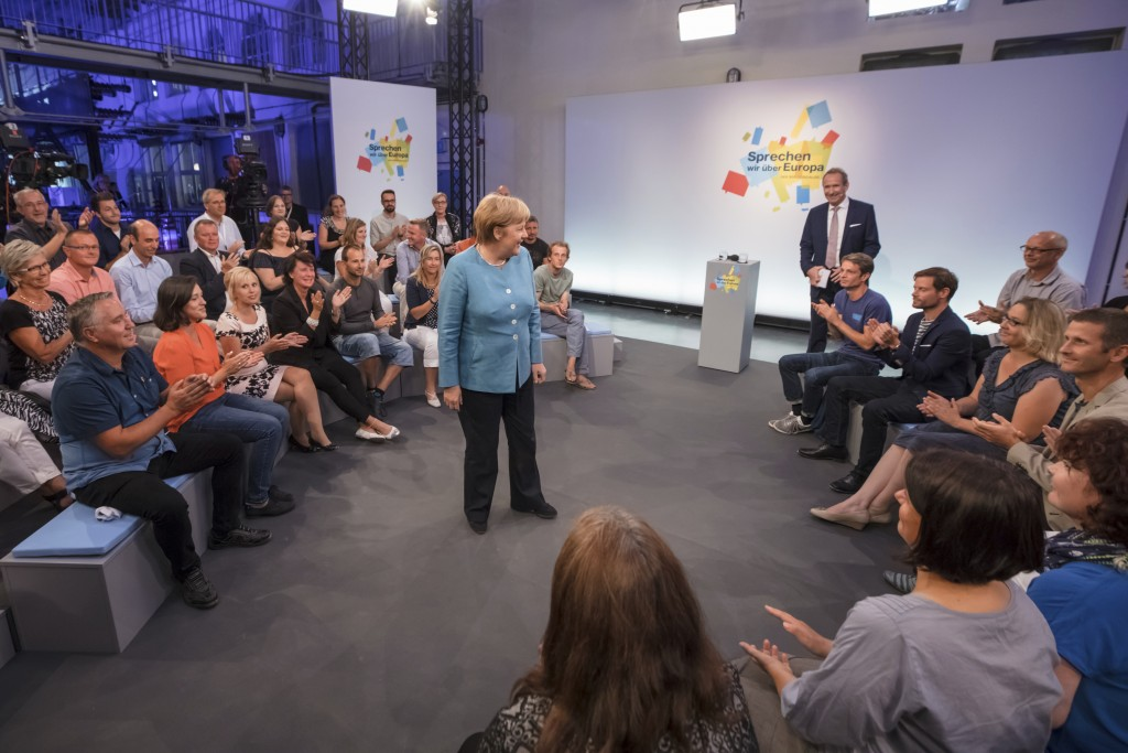 German Chancellor Angela Merkel speaks to invited participants of an event called 'citizen dialogue' in Jena, eastern Germany, Tuesday, Aug. 14, 2018....