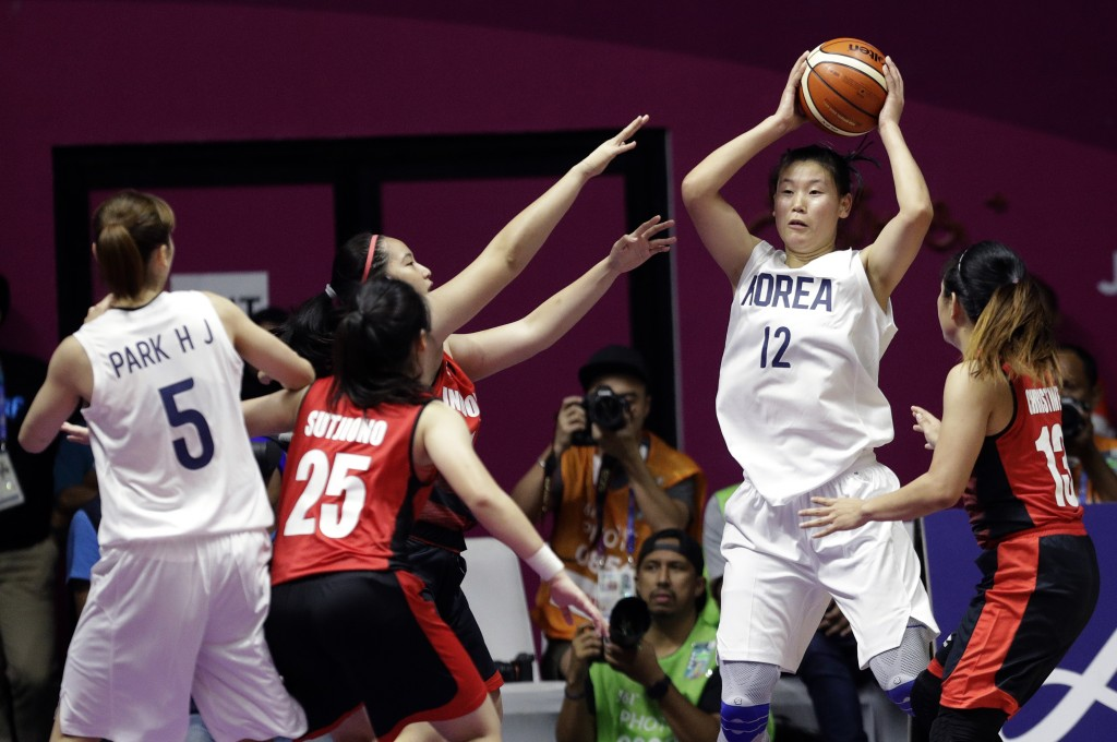 Combined Koreas Ro Suk Yong looks to pass the ball to teammate Park Hyejin, left, during their women's basketball match against Indonesia at the 18th ...