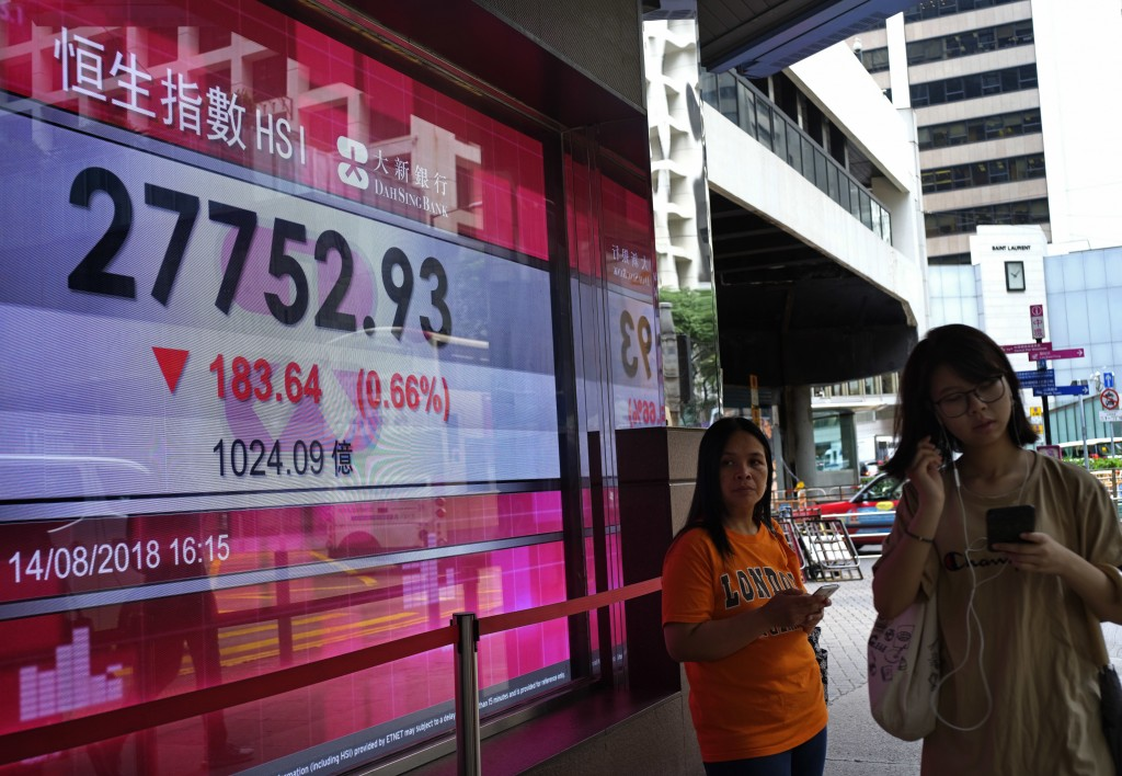 People walk past a bank electronic board showing the Hong Kong share index at Hong Kong Stock Exchange Wednesday, Aug. 15, 2018. Shares were mostly lo...
