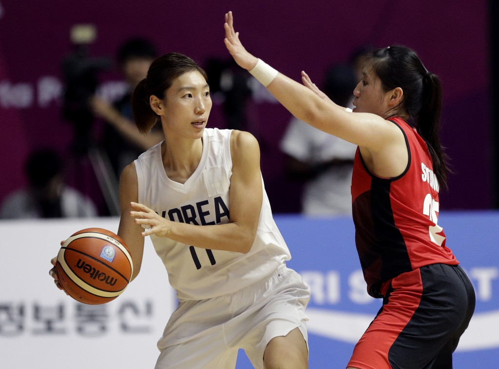 Combined Koreas Lim Yunghui, left, looks for support as Indonesia's Henny Sutjiono attempts to block her throw during their women's basketball match a...