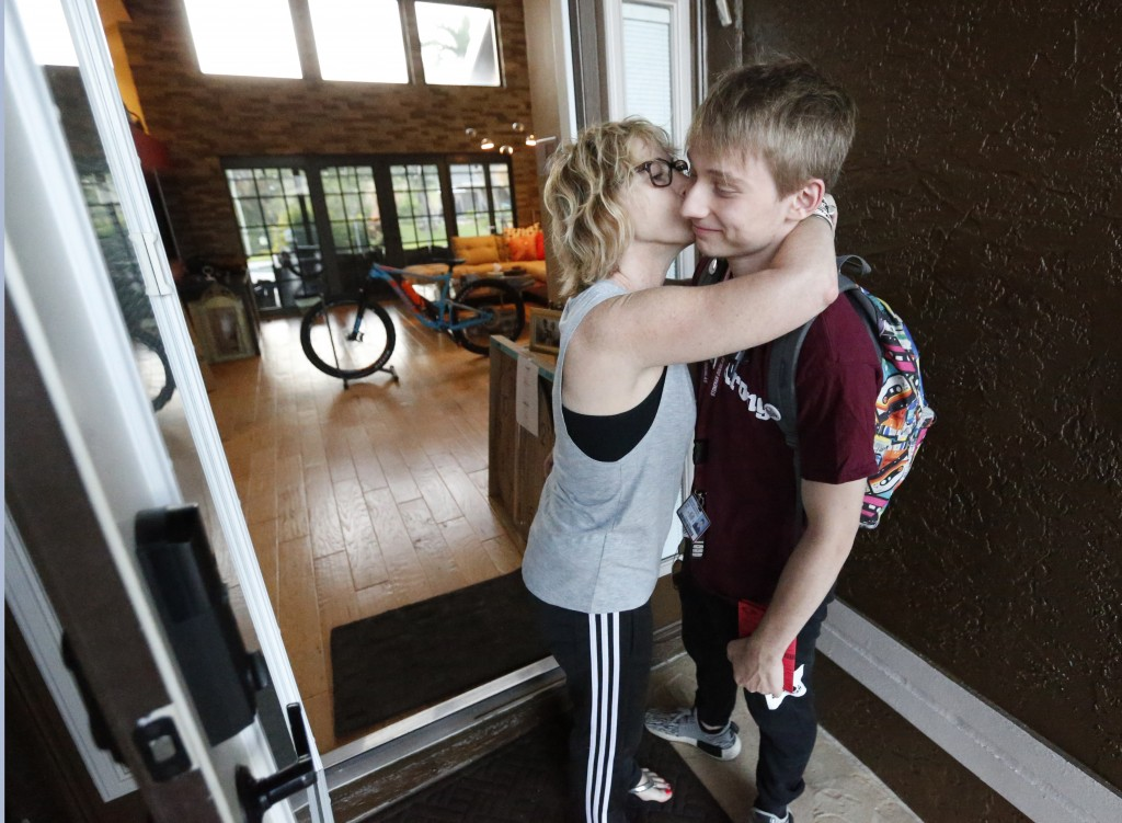 Charlie Shebes, right, 16, a junior at Marjory Stoneman Douglas High School, gets a kiss from his mother Amy as he leaves for school, Wednesday, Aug. ...