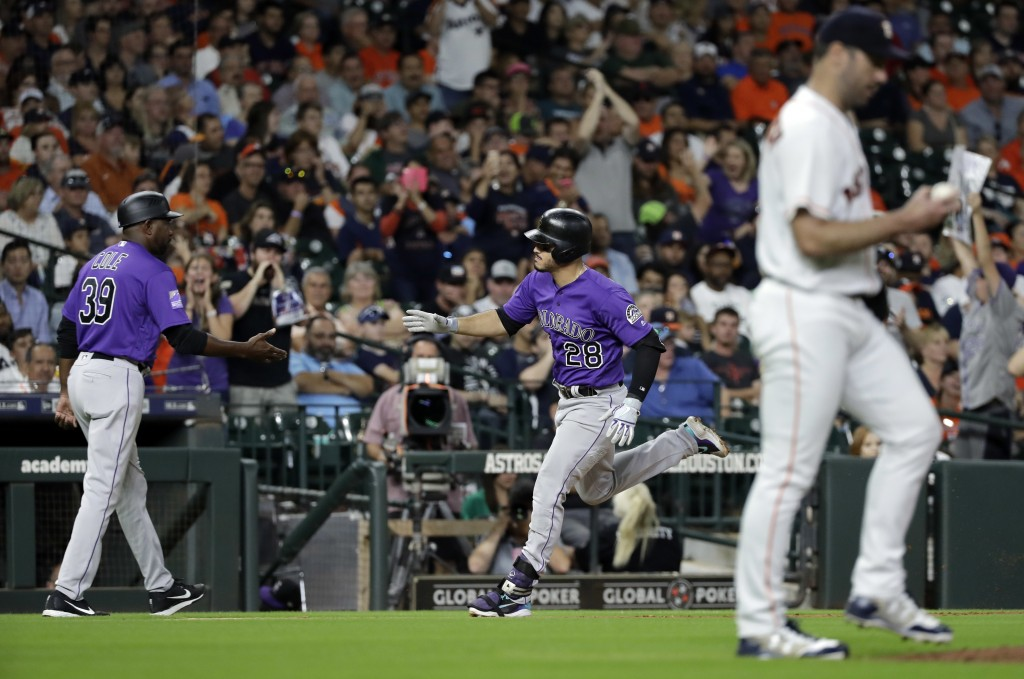 Colorado Rockies' Nolan Arenado (28) is congratulated by third base coach Stu Cole (39) after hitting a two-run home run off Houston Astros starting p...