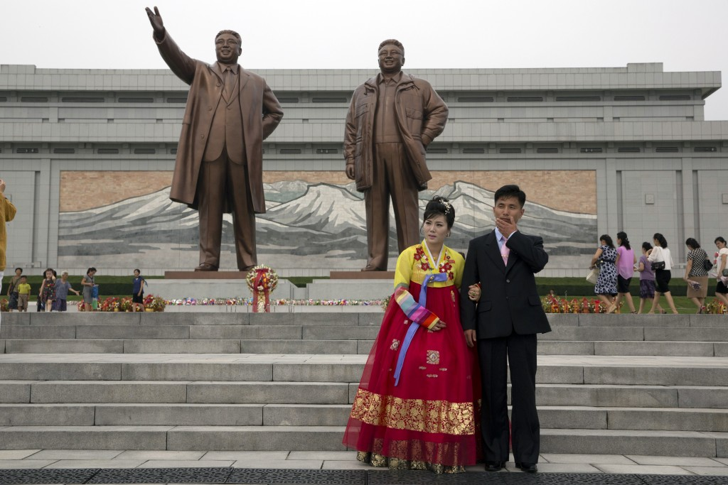 A wedding couple stands near the giant bronze statues of the late North Korean leaders Kim Il Sung and his son Kim Jong Il during the anniversary of t...