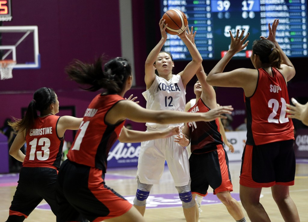 Combined Koreas Ro Suk Yong, centre, looks for support as Indonesian players attempt to block her throw during their women's basketball match at the 1...