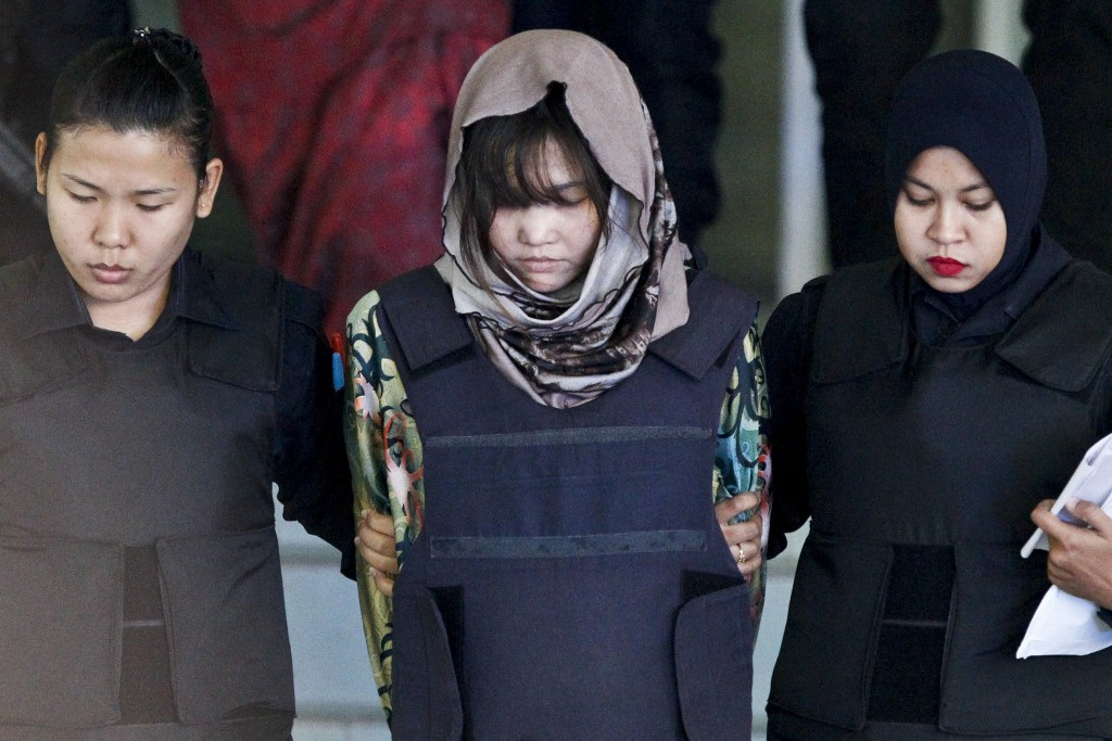 FILE - In this March 22, 2018, file photo, Vietnamese Doan Thi Huong, center, is escorted by police as she leaves after a court hearing at Shah Alam H...
