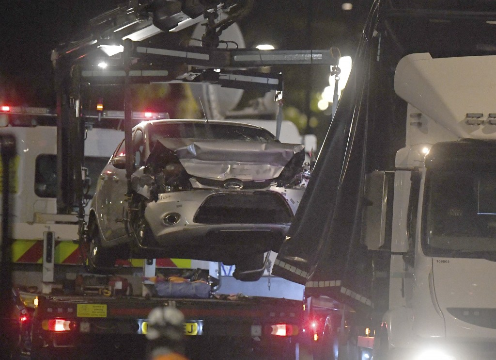 Police recover the car that crashed into security barriers from the scene outside the Houses of Parliament, Westminster in London, Tuesday Aug. 14, 20...