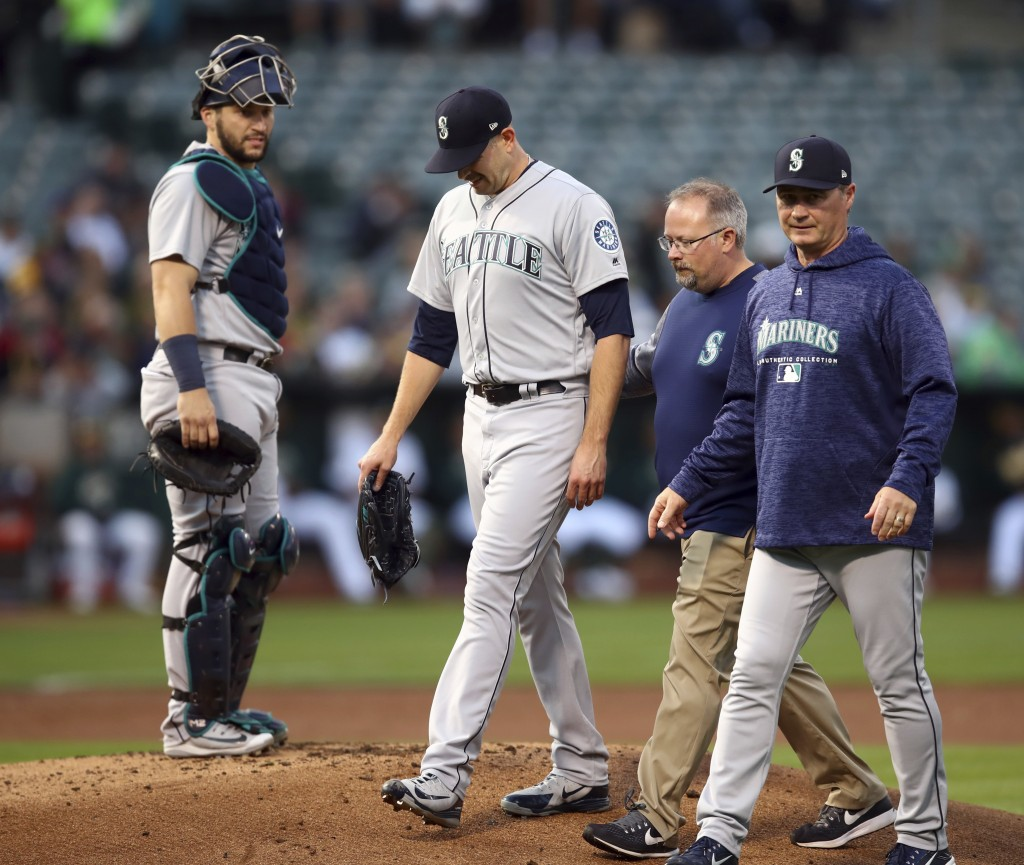 Seattle Mariners pitcher James Paxton, second from left, is escorted off the field after being hit by a ball in the first inning of a baseball game ag...