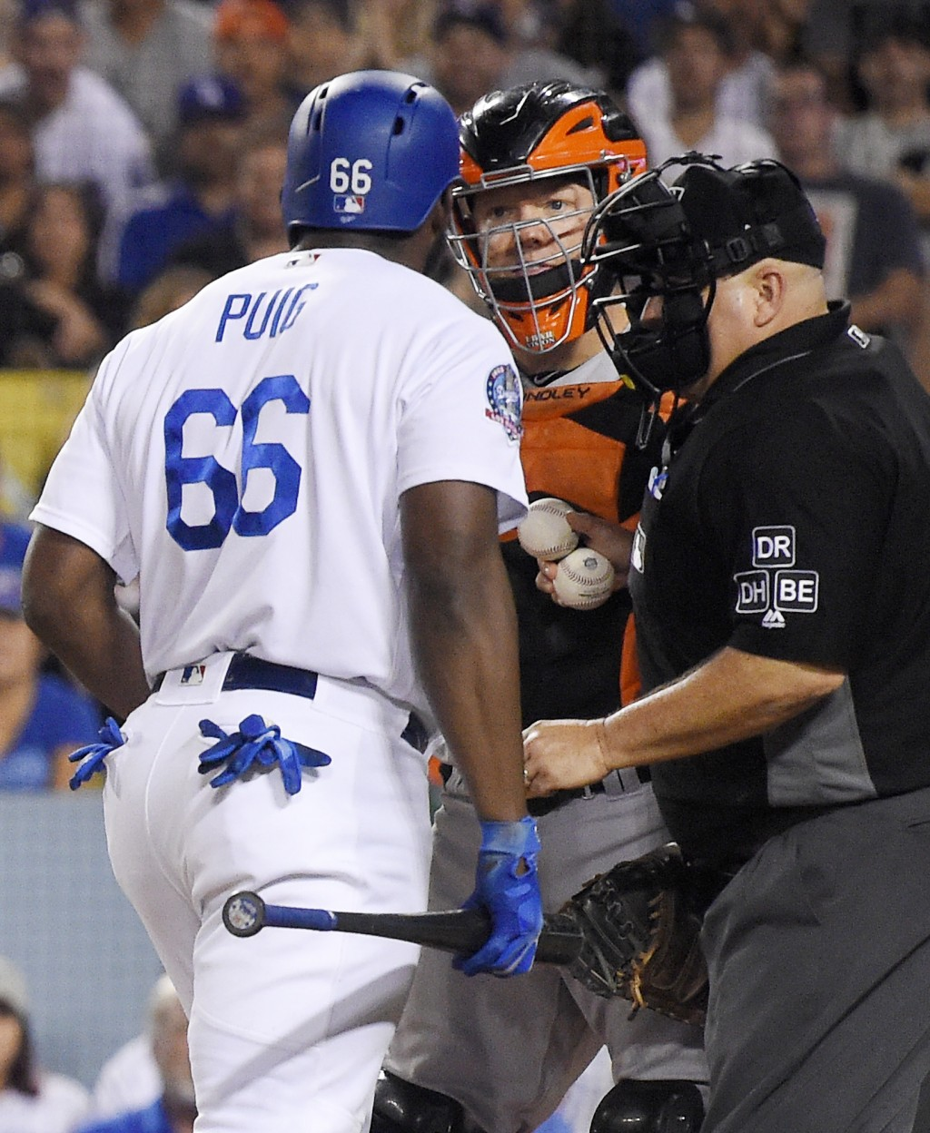 Los Angeles Dodgers' Yasiel Puig, left, and San Francisco Giants catcher Nick Hundley, center, argue while home plate umpire Eric Cooper gets between ...