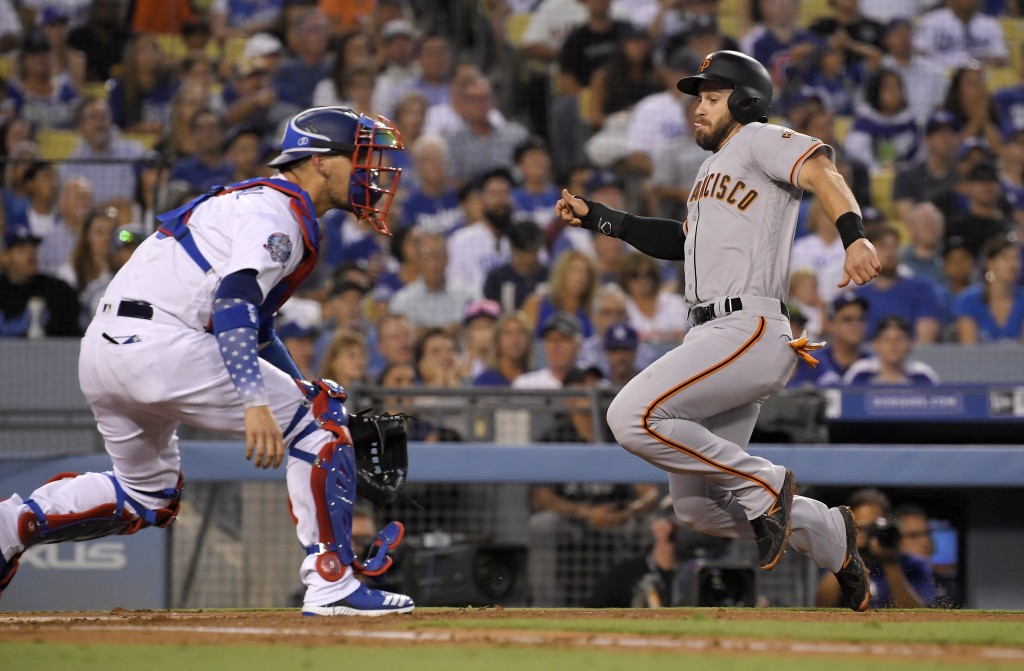 San Francisco Giants' Evan Longoria, right, scores on a single by Alen Hanson as Los Angeles Dodgers catcher Yasmani Grandal waits for the throw durin...