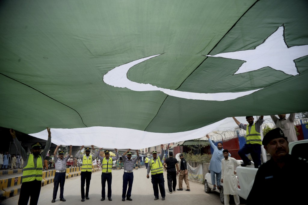 Pakistani police officers hold a national flag during a rally to mark the country's Independence Day, in Peshawar, Pakistan, Tuesday, Aug 14, 2018. Th...