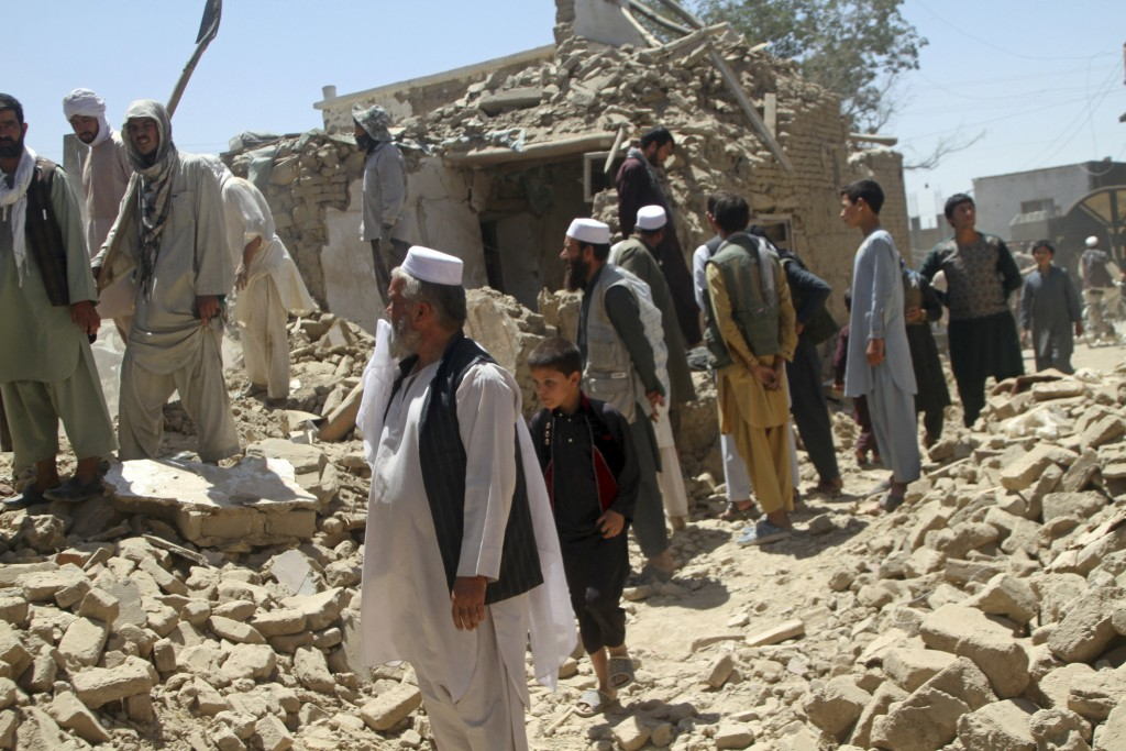 Afghan men stand near a damaged house following a Taliban attack in Ghazni, Afghanistan, Wednesday, Aug. 15, 2018. A Taliban assault on two adjacent c...