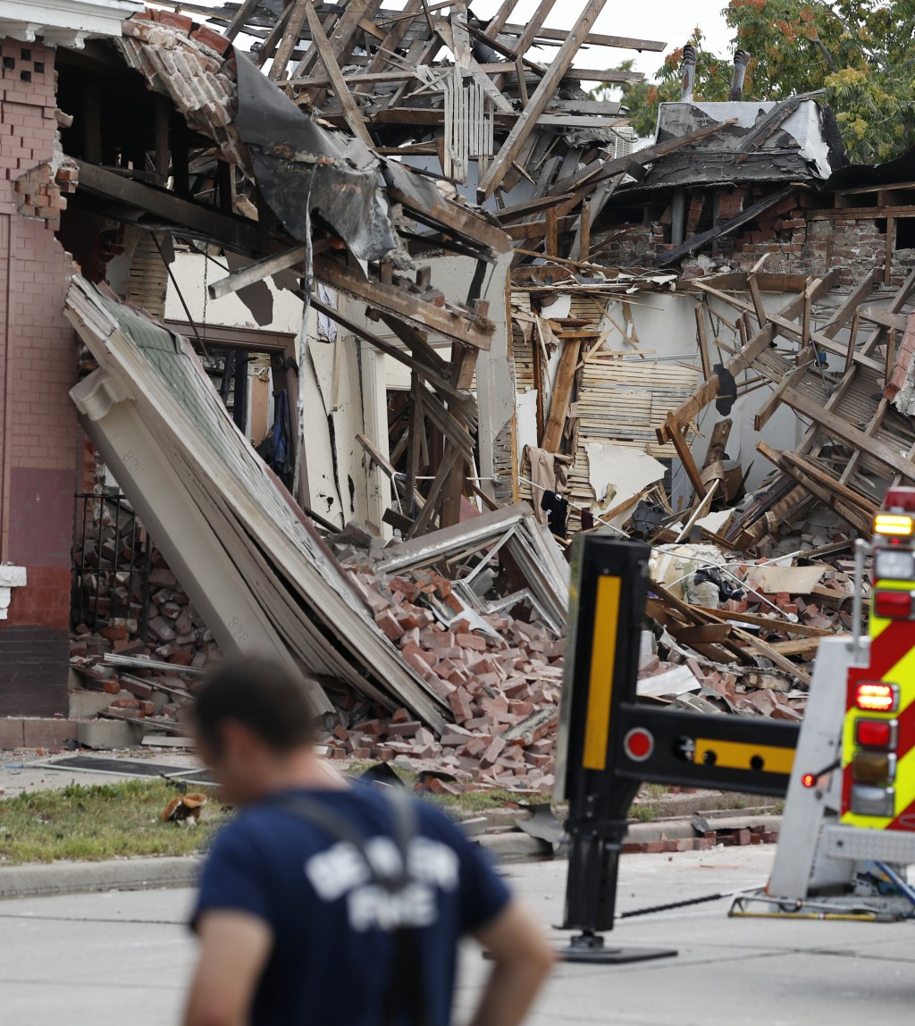 Rubble from an apparent gas explosion in a row of homes is strewn along a block on Santa Fe Boulevard Tuesday, Aug. 14, 2018, in Denver. Fire official...