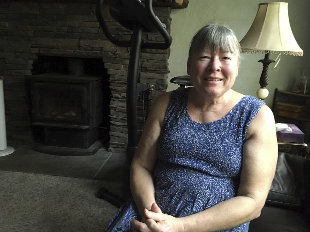 n this Thursday, Aug. 9, 2018 photo, Dawn Bodley, 62, sits in her home near Lakeport, Calif. Fire swept through Bodley's property but firefighters sav...
