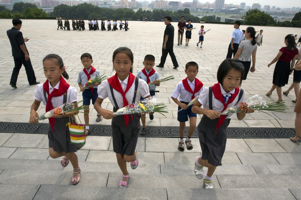 Children hold flowers as they pay their respects before the giant bronze statues of late North Korean leaders Kim Il Sung and his son Kim Jong Il duri...