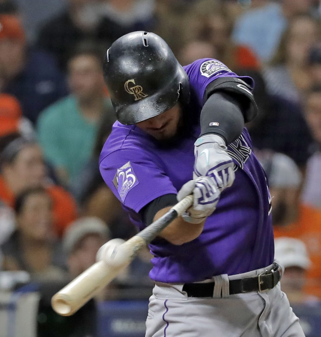 Colorado Rockies' Nolan Arenado hits a two-run home run against the Houston Astros during the sixth inning of a baseball game Tuesday, Aug. 14, 2018, ...