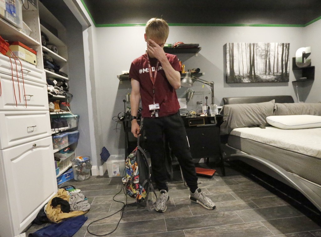 Charlie Shebes, 16, a junior at Marjory Stoneman Douglas High School rubs his eyes, as he prepares to go to school, Wednesday, Aug. 15, 2018, in Parkl...