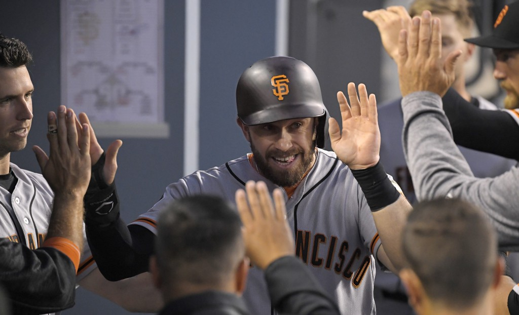 San Francisco Giants' Evan Longoria is congratulated by teammates in the dugout after scoring on a single by Alen Hanson during the second inning of a...