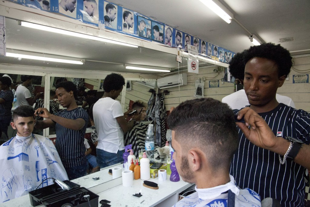 In this Wednesday, Aug. 8, 2018 photo, Eritrean migrant Ghrmay Negassi works at a barbershop in Tel Aviv, Israel. African migrants coming into Israel ...